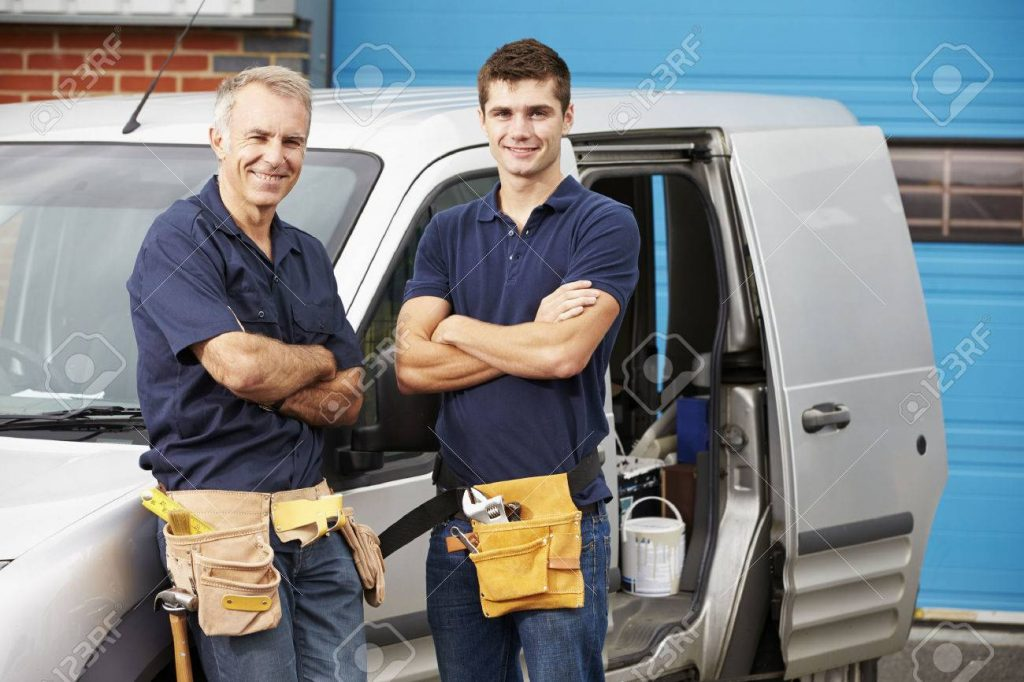 plumbers standing outside of a work vehicle